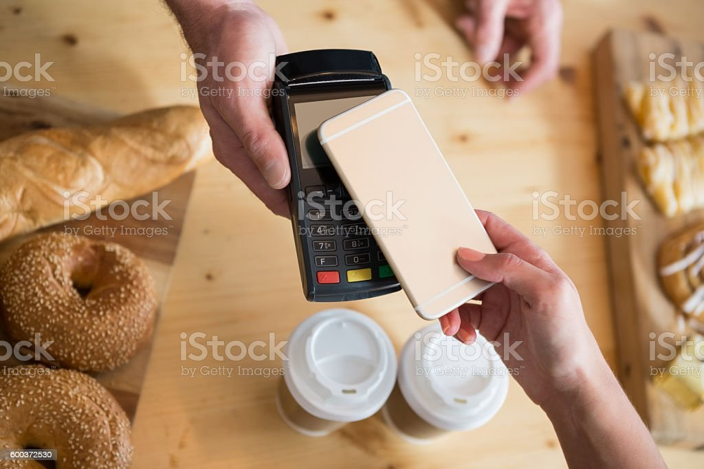 Woman making payment through NFC stock photo