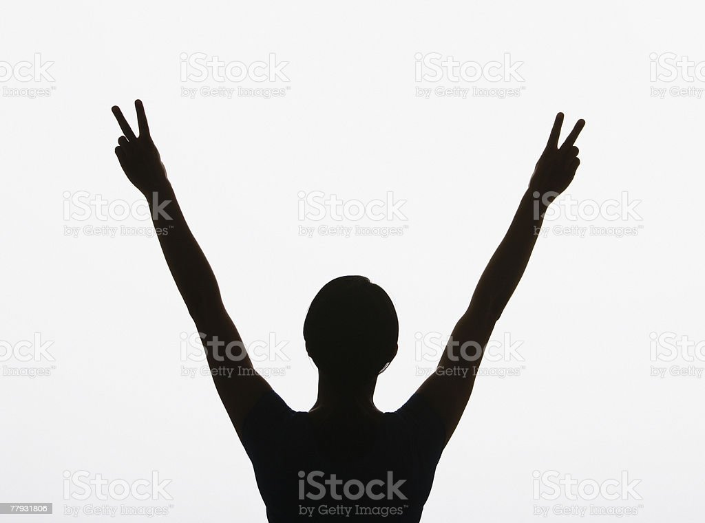 Woman making peace signs with both hands in air royalty-free stock photo