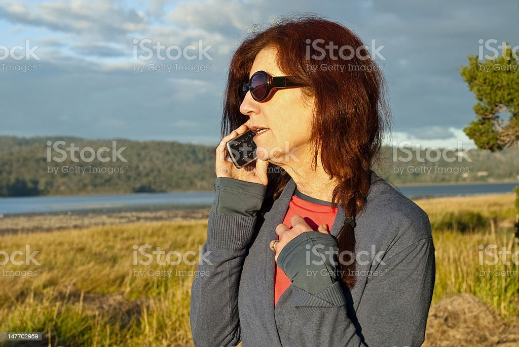 Woman making phone call in golden light royalty-free stock photo