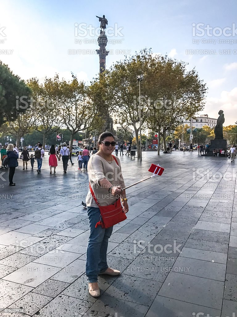Woman making selfie with Columbus monument, Barcelona stock photo