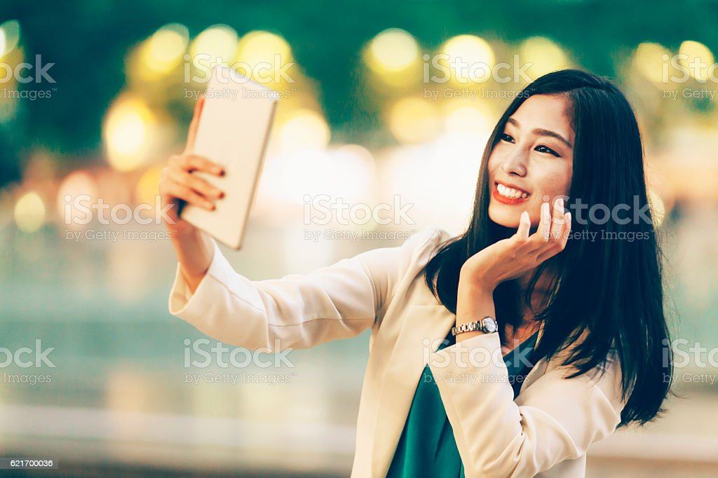 Woman making selfie with digital tablet on street at night stock photo