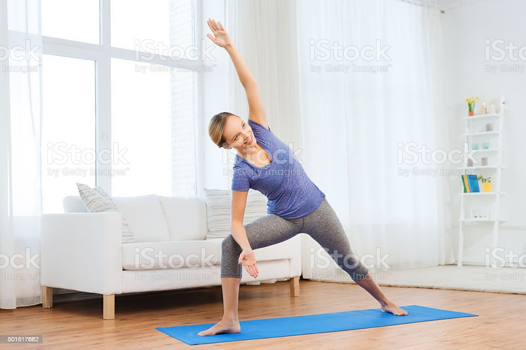 woman making yoga bikram triangle pose on mat stock photo