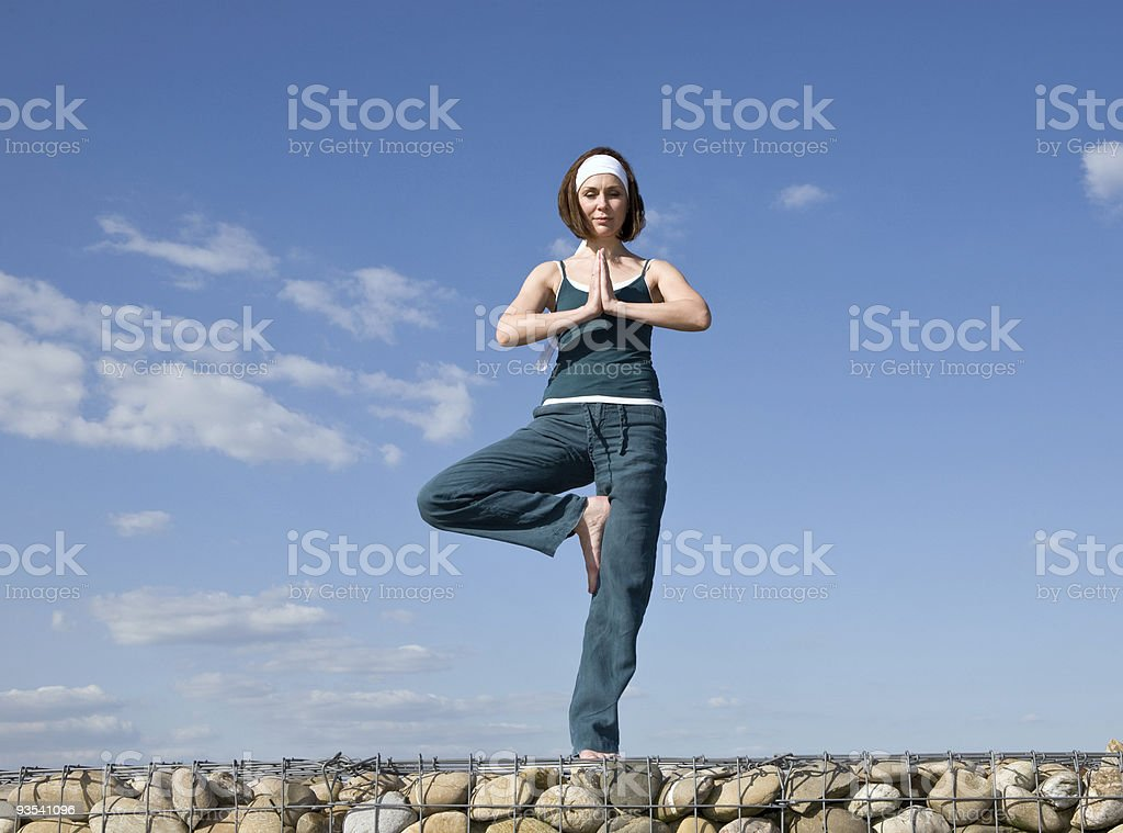 Woman making Yoga exercises in top of a stone wall stock photo