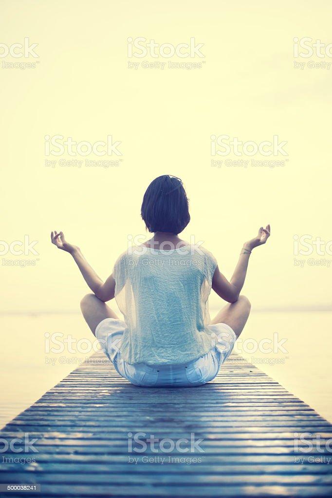 Woman making yoga in a boardwalk stock photo