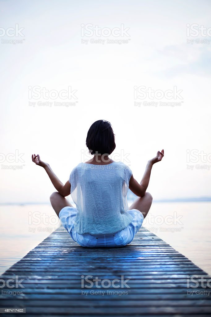 woman making yoga in front of the sea stock photo