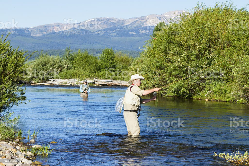 Woman & Man Fly Fishing In A Mountain Steam royalty-free stock photo