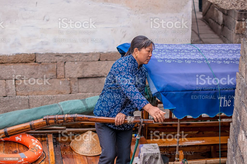 Woman maneuvering a boat stock photo