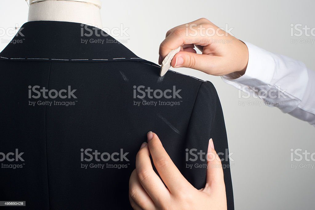 Woman marking Jacket on Male Dress Form stock photo