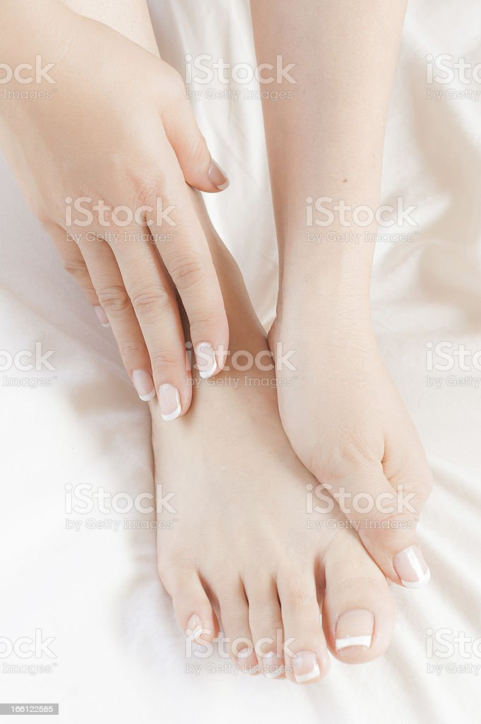 Woman massages own pedicured foot on white sheet stock photo