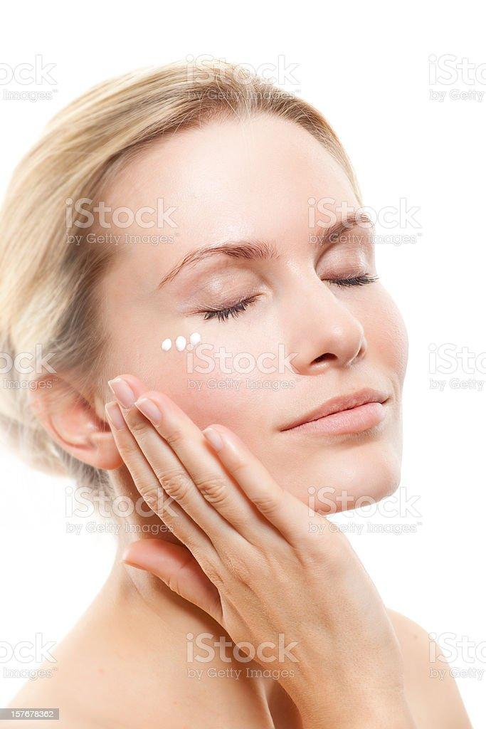 Woman massaging face with facial cream stock photo