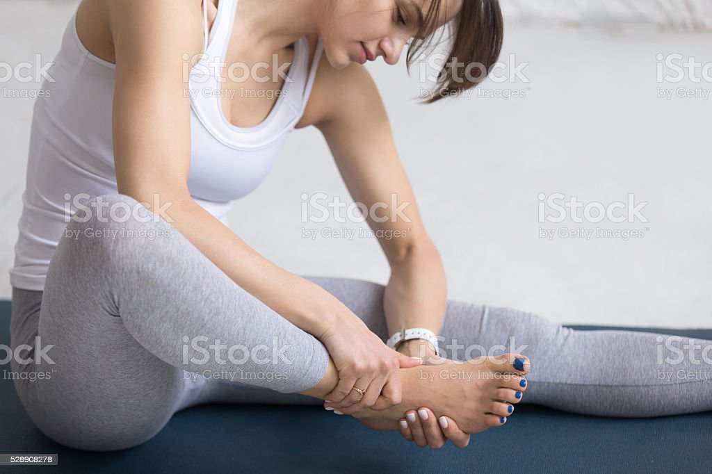 Woman massaging her foot during sport practice stock photo