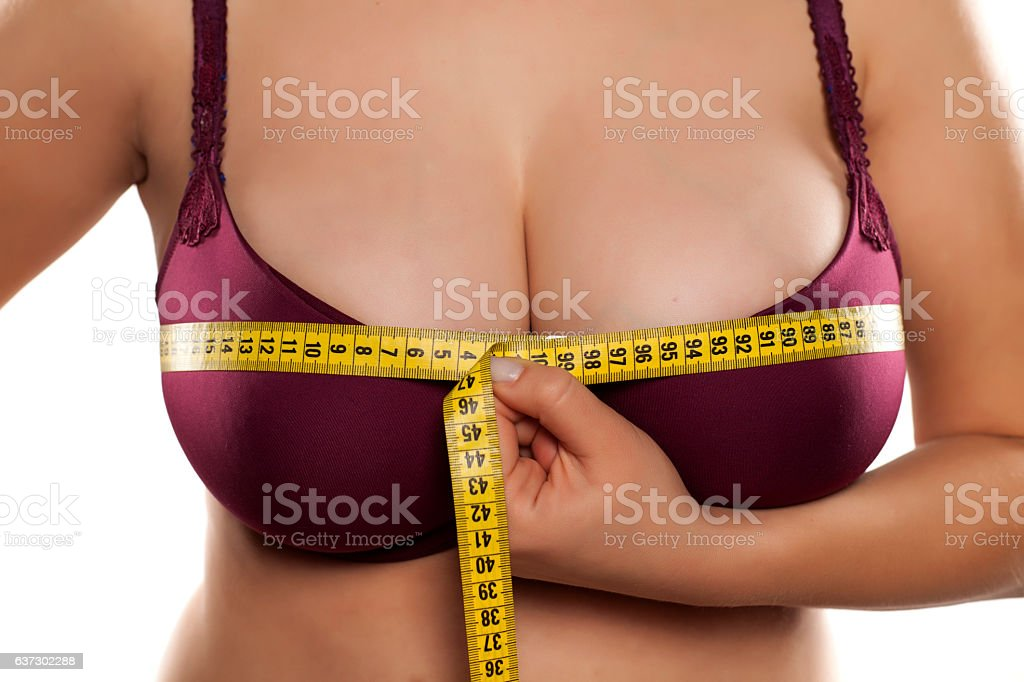 woman measured her breast with a measuring tape stock photo
