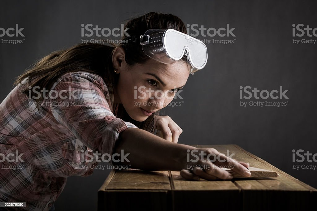Woman measuring a wooden board with a tape measure stock photo
