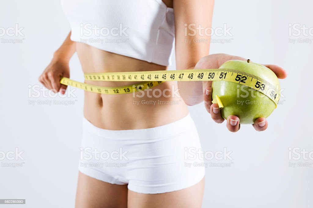 Woman measuring her slim body. Isolated on white background. stock photo