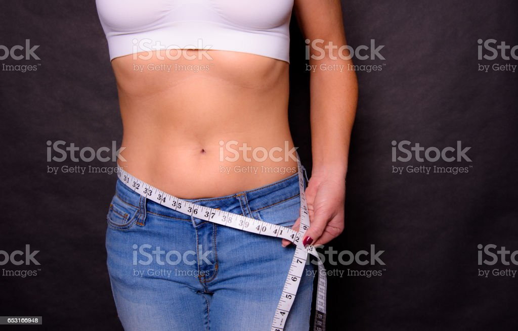 A Woman Measuring Her Waist While Wearing Jeans and A Sports Bra stock photo