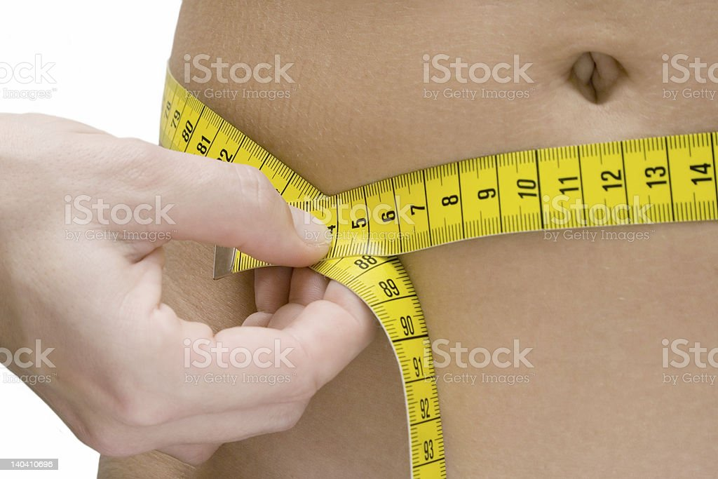Woman measuring her waist with a yellow tape stock photo