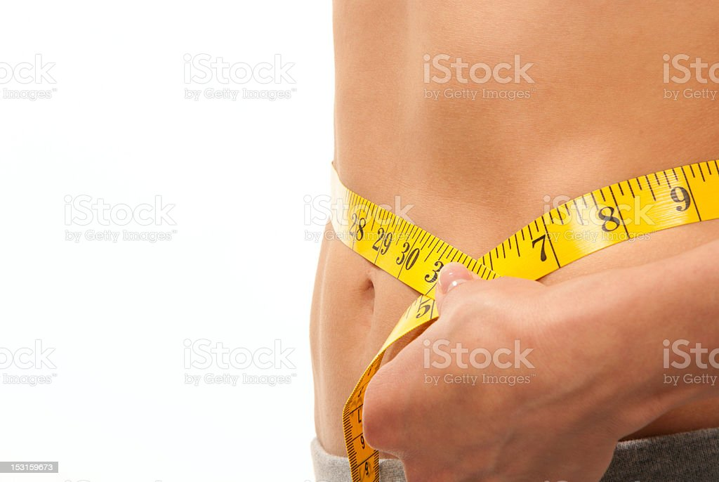 Woman measuring her waist with tape measure royalty-free stock photo