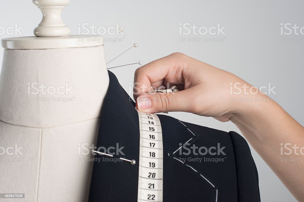 Woman Measuring Jacket on Male Dress Form stock photo