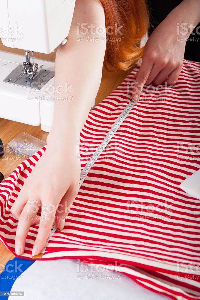 Woman measuring pattern on fabric stock photo