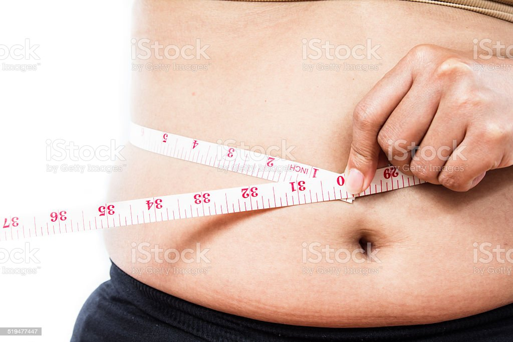 Woman measuring waist line with tape measure stock photo