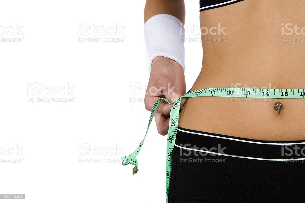 Woman measuring waist using tape measure royalty-free stock photo