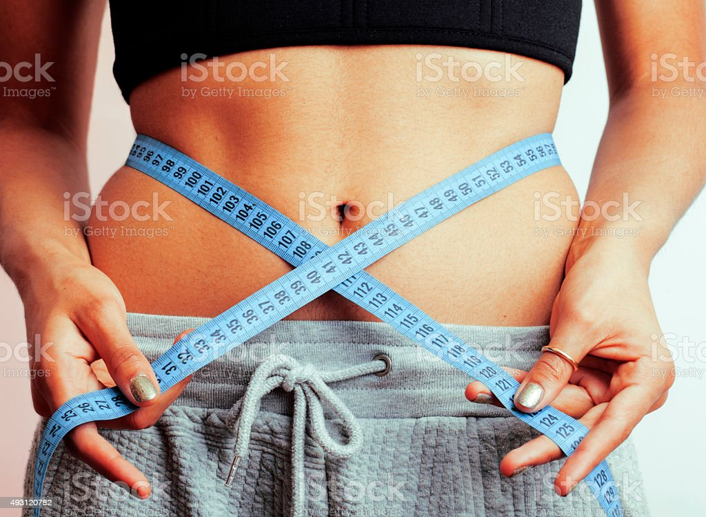 woman measuring waist with tape on knot like a gift stock photo
