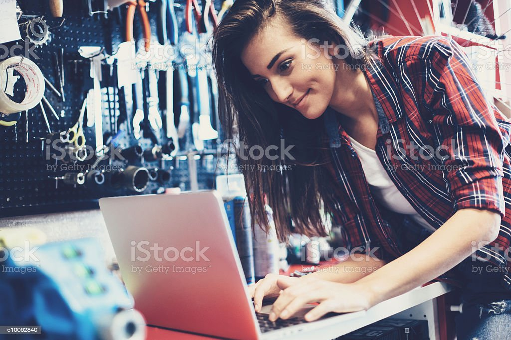 Woman mechanic working on a laptop stock photo