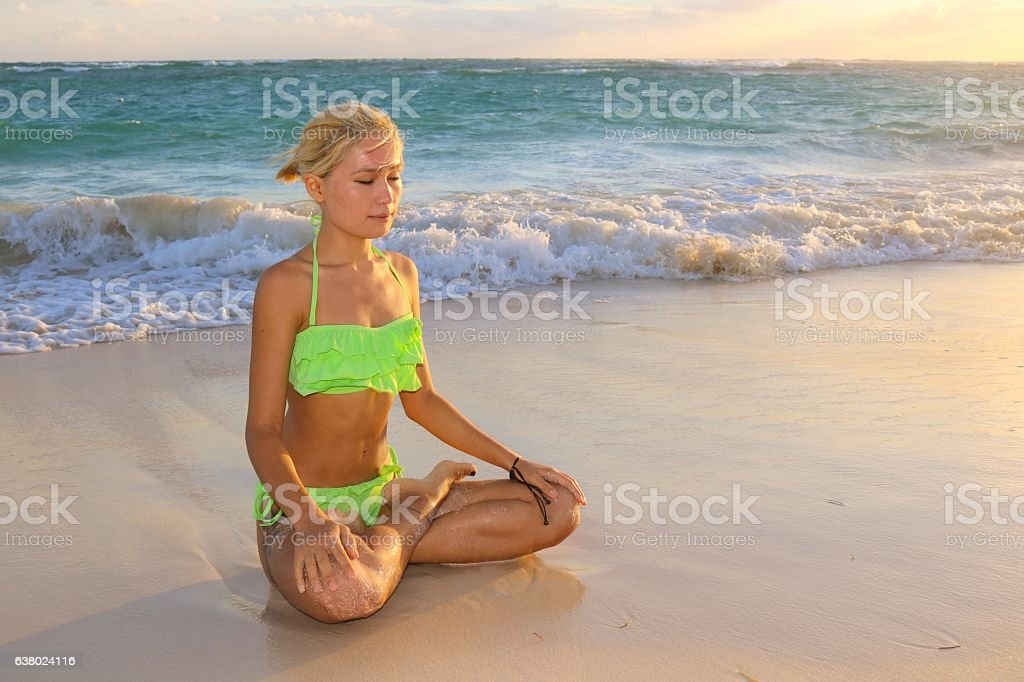 Woman meditates at beach stock photo