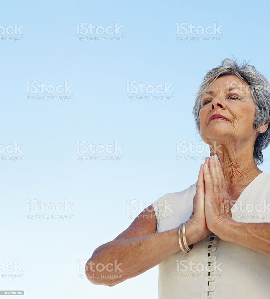 Woman meditating against sky royalty-free stock photo