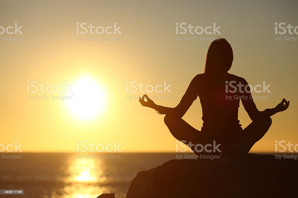 Woman meditating and practicing yoga watching the sun stock photo
