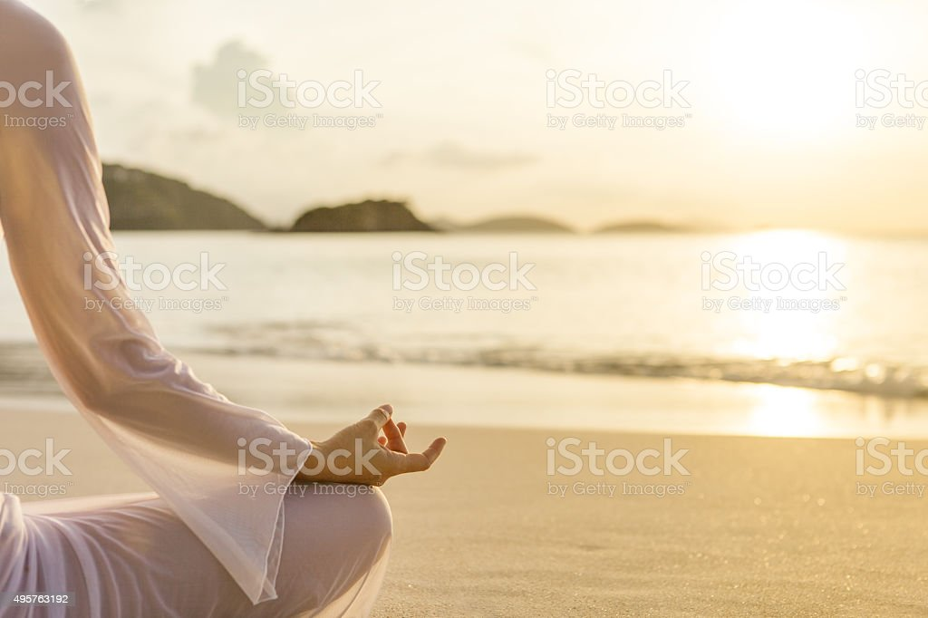 woman meditating at sunset on a beach in the Caribbean stock photo