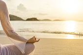 woman meditating at sunset on a beach in the Caribbean