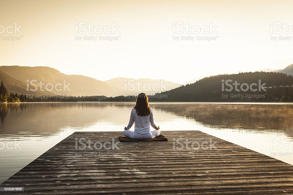 Woman meditating by lake. stock photo