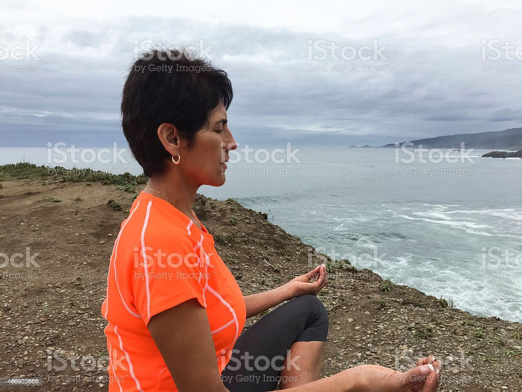 Woman meditating by ocean stock photo