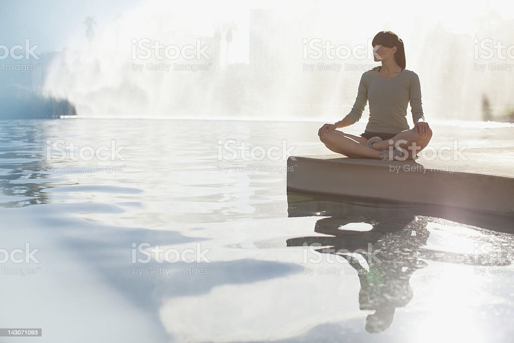 Woman meditating by still pool stock photo