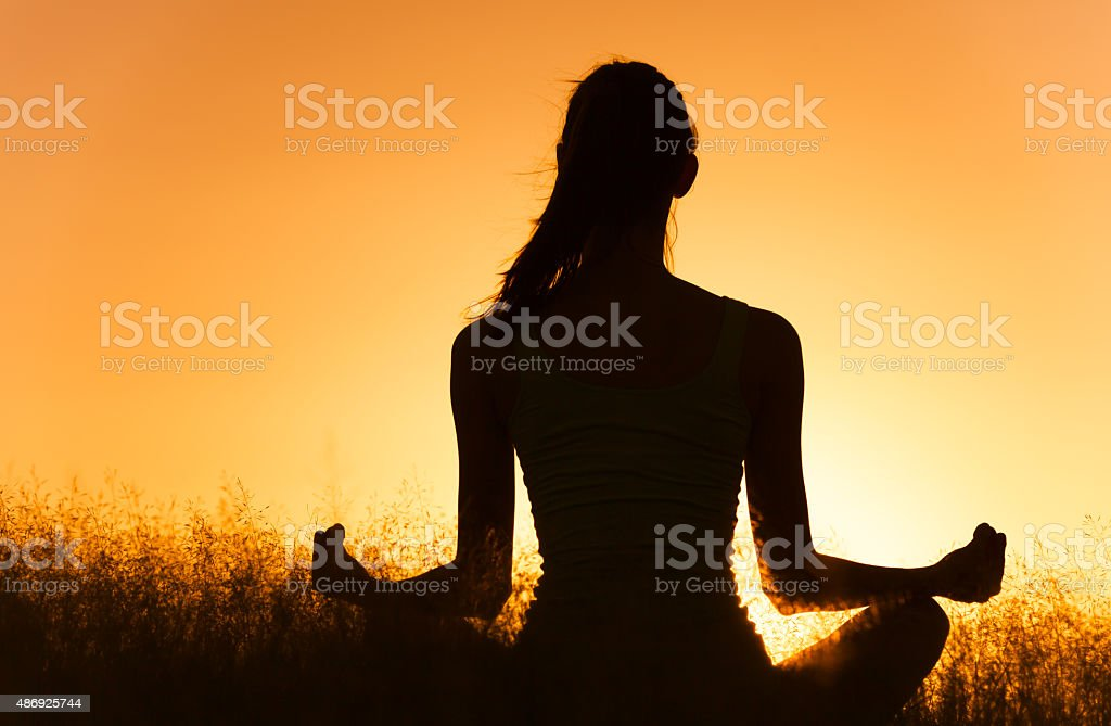 Woman meditating in a peaceful setting. stock photo