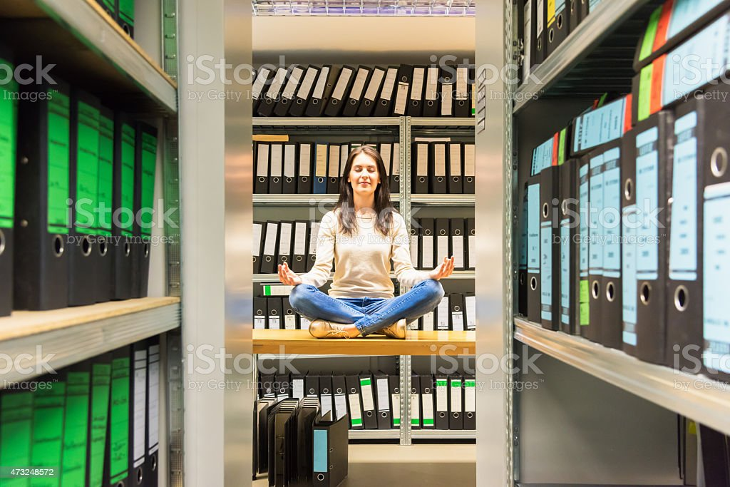 Woman meditating in company finance file archive stock photo