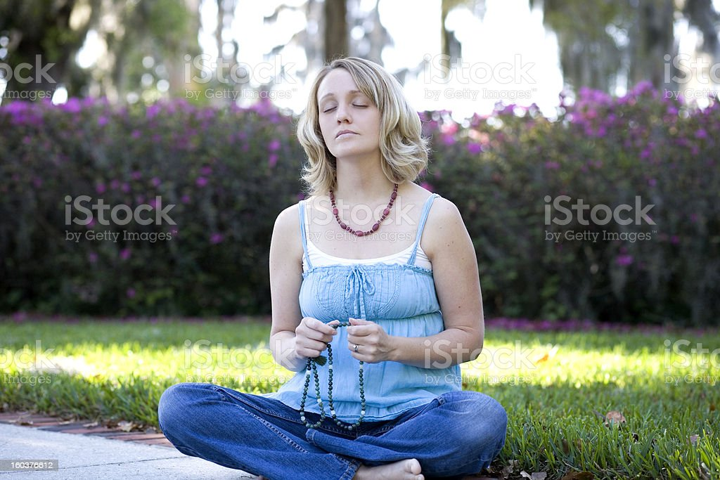 Woman Meditating in Nature with Prayer Beads stock photo
