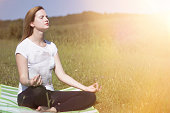 woman meditating in on the hill at the sunlight