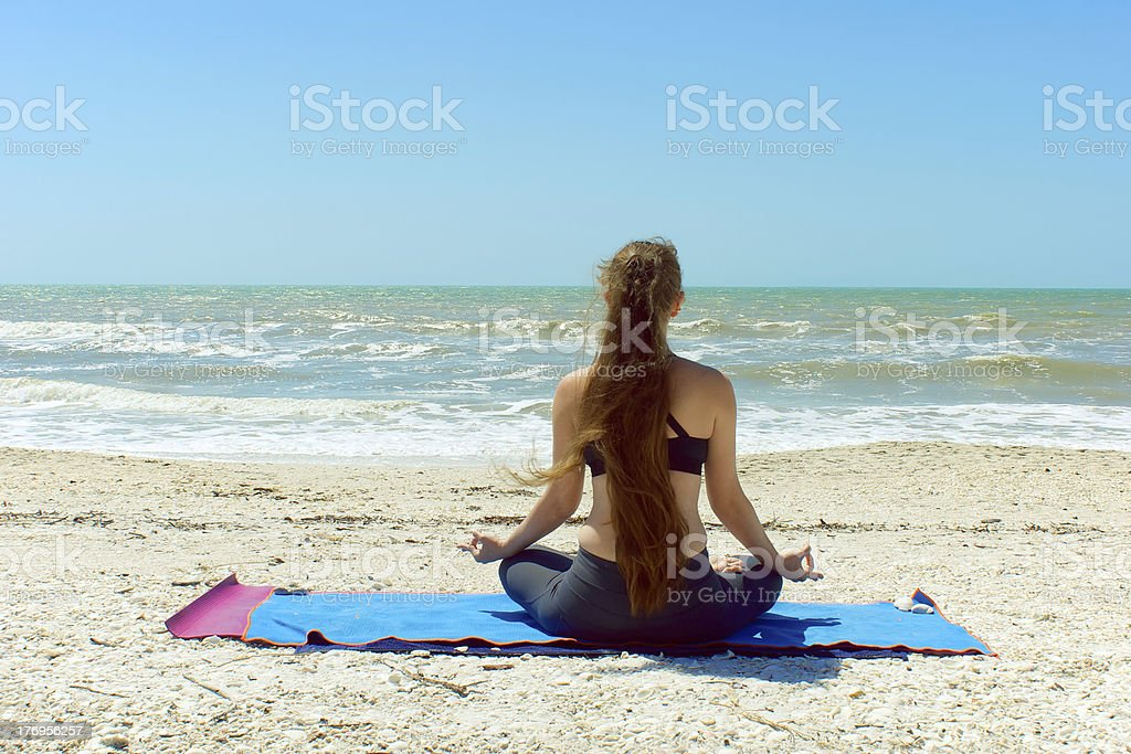 woman meditating in yoga pose outdoors stock photo