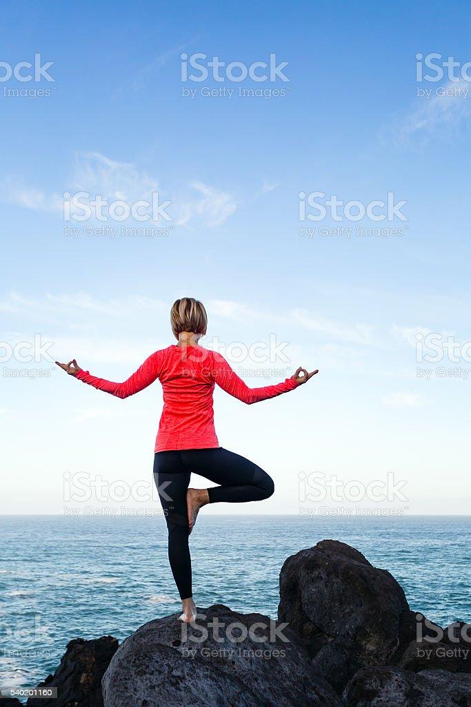 Woman meditating in yoga vrksasana tree pose stock photo