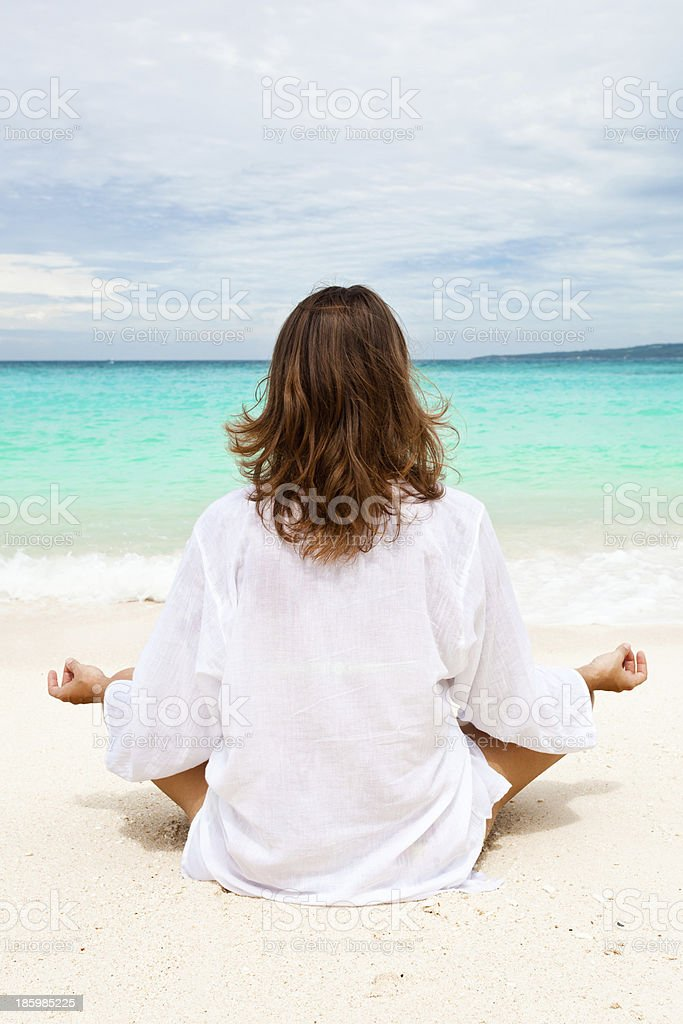 Woman meditating on beach royalty-free stock photo