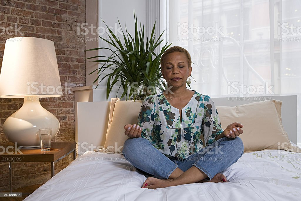 Woman meditating on bed stock photo