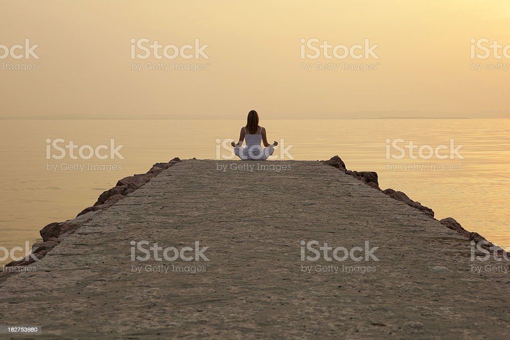 Woman meditating on jetty royalty-free stock photo