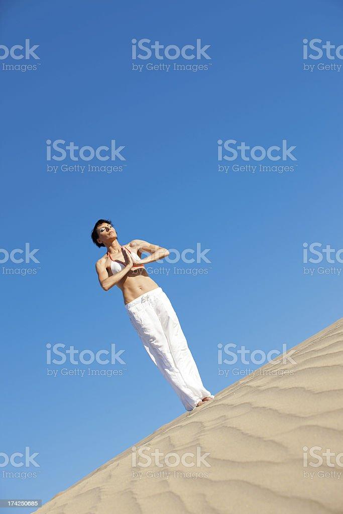 Woman meditating on sand dune royalty-free stock photo