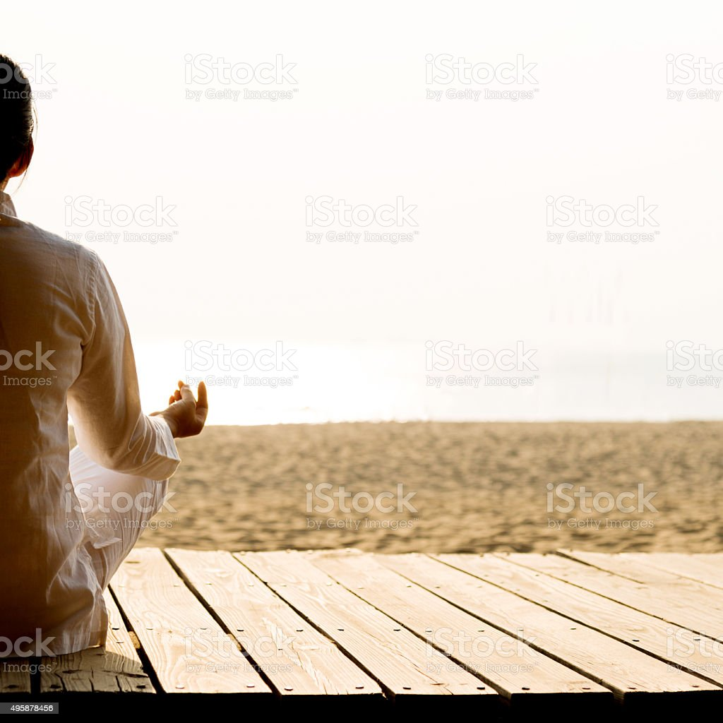 Woman meditating on the beach stock photo