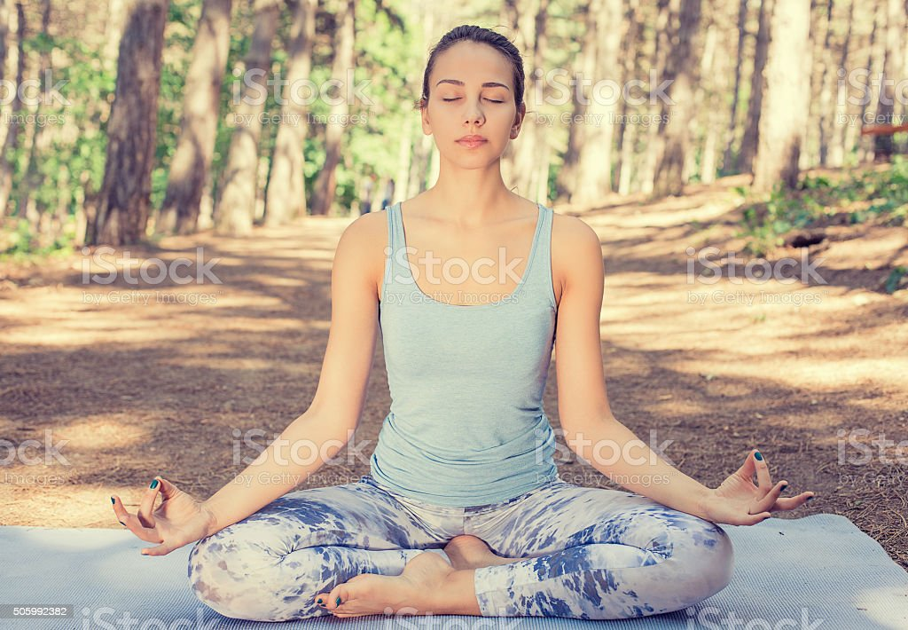Woman meditating outdoors in spring summer park stock photo