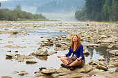 woman meditating sitting on stone in quiet location