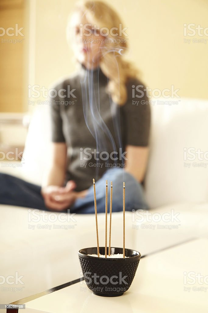 Woman meditating with incense in foreground royalty-free stock photo