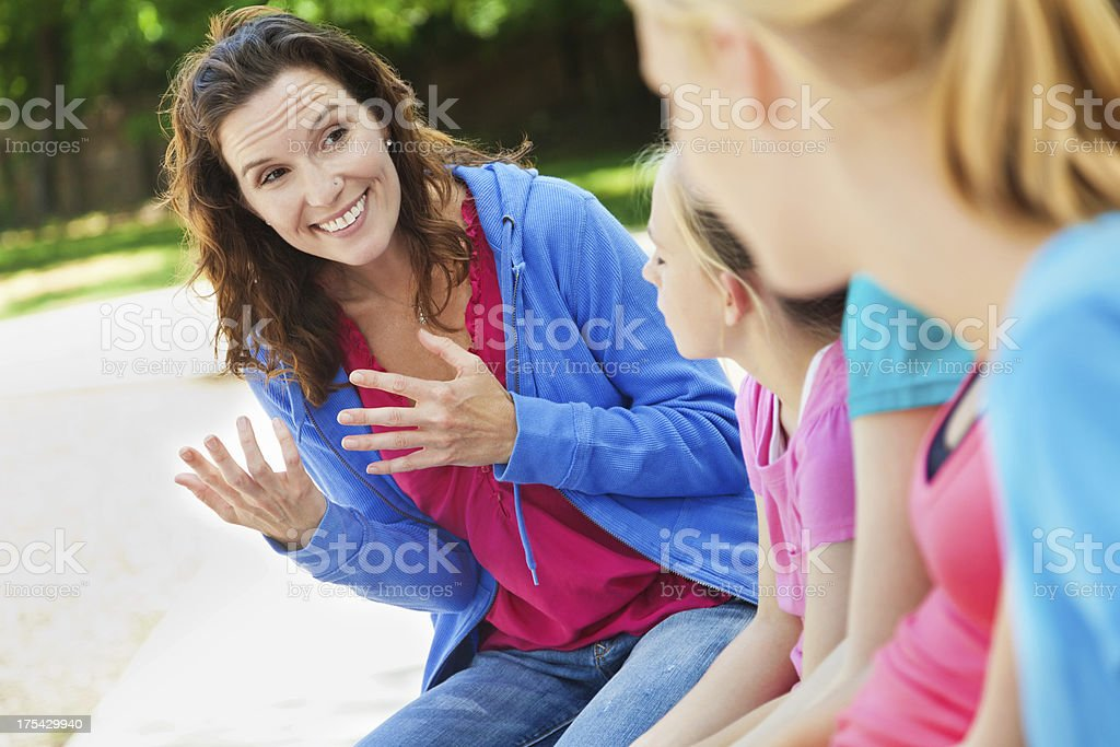 Woman mentoring group of girls at a park royalty-free stock photo